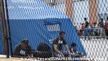 May 31, 2021, Roccella Jonica, Calabria, Italy: Men seen socializing in front of a shelter..Nearly 230 migrants, floating towards Italy, have been rescued by the Italian coast guard and carried in the port town of Roccella Jonica, southern region of Calabria. Women, children and men of different nationalities have been taken to the local first aid centre for assistance and identification. (Credit Image: © Valeria Ferraro/SOPA Images via ZUMA Wire
