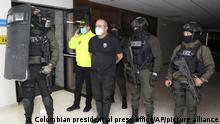 In this photo released by the Colombia Police Press Office, one of the country's most wanted drug traffickers, Dairo Antonio Usuga, alias Otoniel, leader of the violent Clan del Golfo cartel, is handcuffs upon his arrival to Bogota, Colombia, Saturday, Oct. 23, 2021. Colombian security forces have captured the country's most wanted drug trafficker, a rural warlord who evaded a decade long manhunt by corrupting state officials and aligning himself with combatants on the left and right. (Colombia Police Press Office via AP)