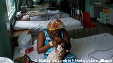 A woman breastfeeds her daughter at the Saint Damien Pediatric Hospital of Port-au-Prince, Haiti, Sunday, Oct. 24, 2021. Haiti's capital has been brought to the brink of exhaustion by fuel shortages and the capital's main pediatrics hospital says it has only three days of fuel left to run ventilators and medical equipment. (AP Photo/Matias Delacroix)