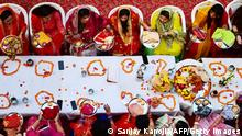 TOPSHOT - Hindu married women offer prayers during celebrations of the Karva Chauth festival, in which married women fast the whole day and offer prayers to the moon for the welfare, prosperity, and longevity of their husbands in Allahabad on October 24, 2021. (Photo by SANJAY KANOJIA / AFP) (Photo by SANJAY KANOJIA/AFP via Getty Images)