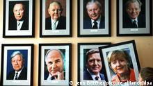 ARCHIV - Das Foto der neuen Bundeskanzlerin Angela Merkel wird am 23.11.2005 in der Gaststätte «KanzlerEck» in Berlin neben den Porträts der bisherigen deutschen Bundeskanzler aufgehängt - v.l. oben: Konrad Adenauer (CDU), Ludwig Erhard (CDU), Georg Kiesinger (CDU), Willy Brandt (SPD), v.l. unten: Helmut Schmidt (SPD), Helmut Kohl (CDU), Gerhard Schröder (SPD). Merkel war am Vortag vom Bundestag zur ersten deutschen Bundeskanzlerin gewählt worden. Am 10.04.2014 regiert Angela Merkel länger als alle SPD-Kanzler, aber nicht so lange wie Kohl. Foto: Jens Büttner dpa (zu dpa «3062 Tage Kanzlerin» am 09.04.2014) +++ dpa-Bildfunk +++