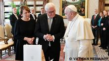 This handout picture taken and released on October 25, 2021, shows German President Frank-Walter Steinmeier (C) and his wife Elke Buedenbender (L) exchanging gifts with pope Francis during a meeting in the Vatican. (Photo by Handout / various sources / AFP) / RESTRICTED TO EDITORIAL USE - MANDATORY CREDIT AFP PHOTO / VATICAN MEDIA - NO MARKETING - NO ADVERTISING CAMPAIGNS - DISTRIBUTED AS A SERVICE TO CLIENTS