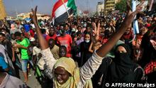Sudanese protesters lift national flags as they rally on 60th Street in the capital Khartoum, to denounce overnight detentions by the army of government members, on October 25, 2021. - Armed forces detained Sudan's Prime Minister over his refusal to support their coup, the information ministry said, after weeks of tensions between military and civilian figures who shared power since the ouster of autocrat Omar al-Bashir. (Photo by AFP) (Photo by -/AFP via Getty Images)