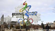 ARCHIV - 29.12.2017, China, Zhangjiakou, Olympia: ein Mann geht an einer Aufsteller mit dem Logo der Olympischen Winterspiele 2022 Peking vorbei. (zu dpa-Meldung: «Auf dem Weg nach Peking 2022: Wirtschaftlich vor, politisch zurück?» vom 23.02.2018) Foto: ---/Kyodo/dpa +++ dpa-Bildfunk +++