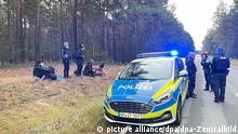 19/10/2021 Podrosche. Bundespolizisten stehen neben einer Gruppe von Migranten, die zuvor über die deutsch-polnische Grenze gegangen waren. (zu dpa «Zuwanderung via Belarus: Seehofer schreibt an Polens Innenminister») +++ dpa-Bildfunk +++