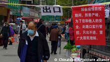 A man wearing a face mask to help curb the spread of the coronavirus walks by a note which reads one-way policy on a street as a measure of pandemic control in Lanzhou city in northwest China's Gansu province, Monday, Oct. 25, 2021. A northwestern Chinese province heavily dependent on tourism closed all tourist sites Monday after finding new COVID-19 cases. (Chinatopix via AP)