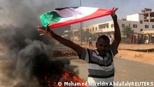 A protester waves a flag during what the information ministry calls a military coup in Khartoum, Sudan, October 25, 2021. REUTERS/Mohamed Nureldin Abdallah