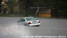 A car is stuck in a flooded street due to Hurricane Rick in Lazaro Cardenas, Mexico, Monday, Oct. 25, 2021. Hurricane Rick roared ashore along Mexico's southern Pacific coast early Monday with winds and heavy rain amid warnings of potential flash floods in the coastal mountains. (AP Photo/Armando Solis)
