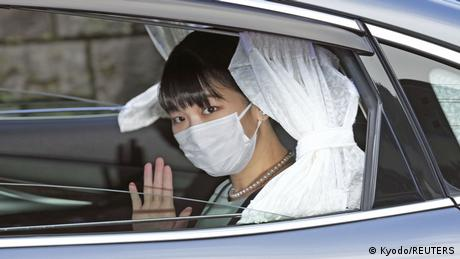 Japan's Princess Mako waves from inside a car as she leaves her home for her marriage in Akasaka Estate in Tokyo