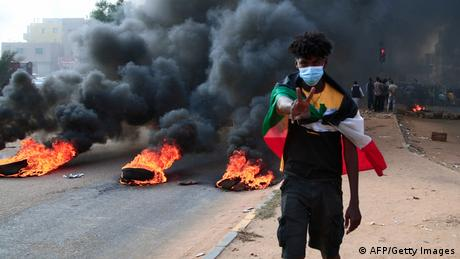 A masked Sudanese protester signalling victory as tires burn in the background