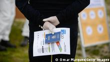CZERWINSK NAD WISLA, POLAND - MAY 28: A seasonal worker from Ukraine wears protective plastic gloves as she holds her passport before being tested for COVID 19 during the ongoing coronavirus crisis on May 28, 2020 in Czerwinsk nad Wisla, Poland. Farmers across Poland, who depend on foreign, seasonal workers to harvest, face a serious labour shortage following the closure of borders due to the COVID-19 pandemic. Poland's strawberry basin (North area of Masovian Voivodeship) is now facing an estimated 70% cut in workforce putting a thread to the strawberry crops. Apart from the shortage of foreign workforce, Polish agriculture suffers from what is considered the worst drought of the last decades. (Photo by Omar Marques/Getty Images)