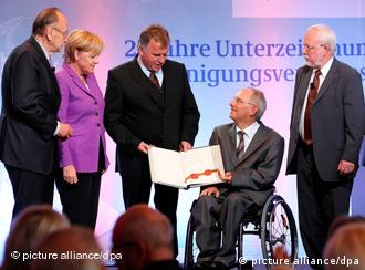 Merkel and others look at Unity Treaty at ceremony