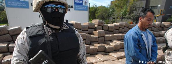 Mexican policeman guarding drugs haul
