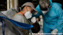An Italian doctor carries out a COVID-19 test for a 7-week-old baby onboard the Geo Barents, a rescue vessel, at the port of Augusta, on the island of Sicily, Italy, Wednesday, Sept. 29, 2021. (AP Photo/Samy Magdy)