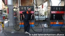 A worker leans against a gasoline pump that has been turned off, at a gas station in Tehran, Iran, Tuesday, Oct. 26, 2021. Gas stations across Iran on Tuesday suffered through a widespread outage of a system that allows consumers to buy fuel with a government-issued card, stopping sales. One semiofficial news agency referred to the incident as a cyberattack. (AP Photo/Vahid Salemi)