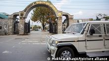 A paramilitary vehicle passes the front gate of Government Medical College in Srinagar, Indian controlled Kashmir, Tuesday, Oct. 26, 2021. Police have registered two separate cases under harsh anti-terror law against students and some staff of two medical colleges for celebrating Pakistan's victory over archrival India in a T20 World Cup cricket game. (AP Photo/Mukhtar Khan)