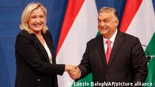 French far-right leader Marine le Pen shakes hands with Hungarian Prime Minister Viktor Orban after a joint press conference