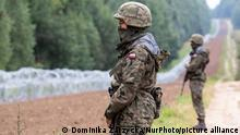 Polish Army Soldiers guard a fence at the Belarusian border