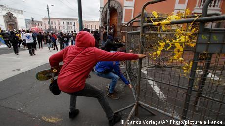 A demonstrator pulls on a barricade