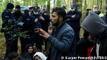 FILE PHOTO: Iraqi migrants talk to NGO Grupa Granica's representatives as they are surrounded by border guards and police officers after they crossed the Belarusian-Polish border during the ongoing migrant crisis, in Hajnowka, Poland October 14, 2021. REUTERS/Kacper Pempel/File Photo