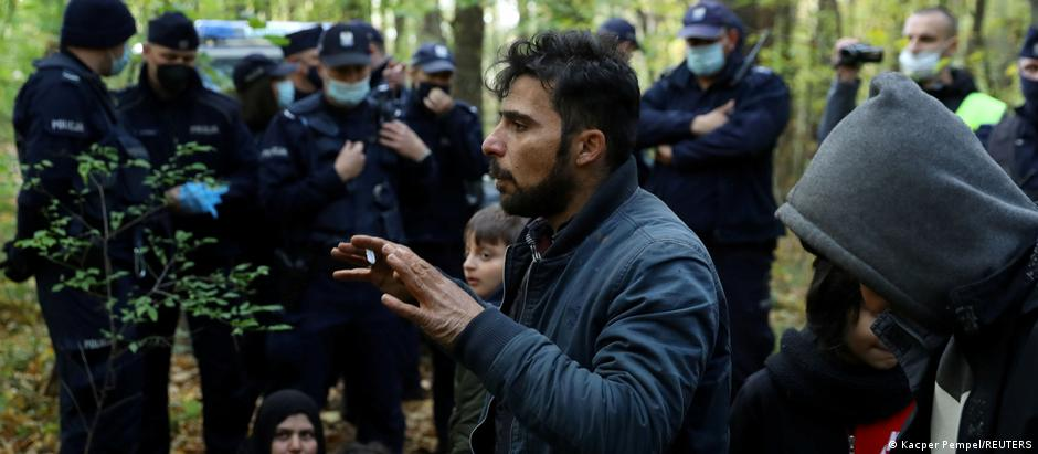 A group of migrants standing in a forest with border guards around them