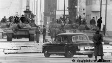 Gespannte Situation wenige Wochen nach dem Mauerbau: Sowjetische Panzer vom TypT54 stehen am 28.10.1961 am Sektorengrenzübergang für Diplomaten und Ausländer in der Friedrichstraße, etwa 150 Meter hinter der Grenzlinie in Ostberlin. Vorn ein Diplomatenwagen kurz vor der Slalomsperre. Am Tag zuvor hatten mehrere amerikanische Panzer unmittelbar an der Grenzlinie zwischen West- und Ostberlin Aufstellung genommen. Anlass für die brisante Konfrontation war die Aufforderung der DDR-Grenzposten an Angehörige der US-Mission, sich beim Passieren des alliierten Kontrollpunktes auszuweisen. Am 29. Oktober entspannte sich die Lage wieder. Für Alliierte Zivilpersonen galt fortan eine Ausweispflicht.