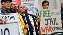 Manifestantes com cartazes com o rosto de Julian Assange
