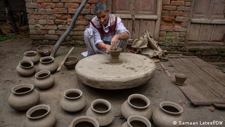 Muhammad Jamal Kumhar, 70, molds the clay into a pot at Larm-Ganjipora village in south Kashmir's Anantnag district