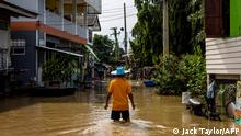 A man wades through floodwaters in a neighbourhood in Ayutthaya on October 4, 2021, after tropical storm Dianmu caused flooding in 31 provinces across the country. (Photo by Jack TAYLOR / AFP)