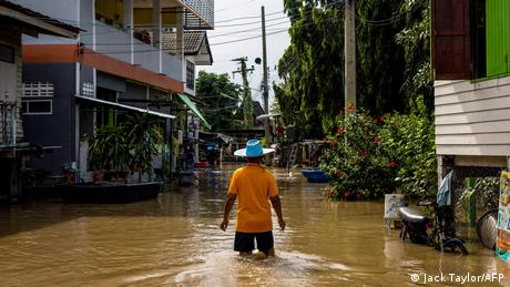 A man wades through floodwaters in a neighborhood in Ayutthaya in Thailand