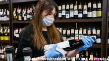 MOSCOW, RUSSIA - APRIL 3, 2020: A vendor in a face mask and gloves holds a bottle of wine at the Food City wholesale and retail food market off Kaluzhskoye Shosse Motorway in the Novomoskovsky Administrative District of Moscow during the pandemic of the novel coronavirus (COVID-19). The market, which continues to operate during the coronavirus lockdown in the Russian capital, has introduced extra safety measures, including disinfection of its premises using chlorine, oxygen and alcohol-based solutions.