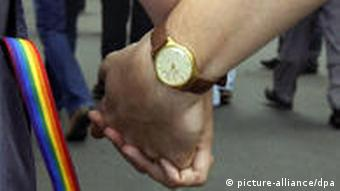 Two men's hands linked with a ranbow band