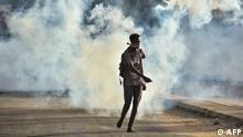 Eine Person geht auf einer Straße, das Gesicht mit einem Tuch bedeckt, im Hintergrund Tränengaswolken