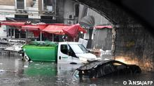 This photo taken on October 26, 2021 and obtained from Italian news agency Ansa on October 27, 2021 sows a car and a garbage truck submerged under the arches of the Marina, near Catania's fish market, in Catania, Sicily, after heavy rain hit the city and the province. (Photo by STRINGER / ANSA / AFP) / Italy OUT