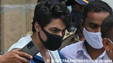 Aryan Khan (C), son of Bollywood actor Shah Rukh Khan, is escorted to court by Narcotics Control Bureau (NCB) officials for a bail plea hearing in Mumbai on October 8, 2021, after his arrest in connection with a drug case. (Photo by Punit PARANJPE / AFP) (Photo by PUNIT PARANJPE/AFP via Getty Images)