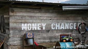 A sign says Money Changer outside of a rural currency exchange facility