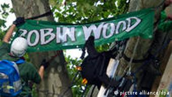 Protestor hangs a Robin Wood banner on a tree