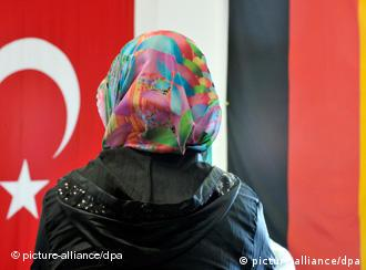 A woman with a headscarf stands in front of German and Turkish flags
