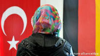 A woman in a headscarf sits in a mosque looking at a German and a Turkish flag, side by side