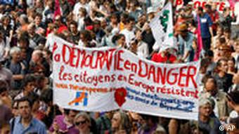Protestors rally in Paris, with a banner saying that the deportations put Democracy in danger.