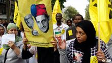 Protesters hold a banner reading No to State Racism and a doctored image of President Nicolas Sarkozy in a fez, at a march to protest French President Nicolas Sarkozy's security policies, including the recent expulsions of Gypsies, or Roma, in Paris, Saturday, Sept. 4, 2010. A whistle-blowing, drum-beating crowd of thousands demonstrated in Paris on Saturday against expulsions of Gypsies as well as other new security measures adopted by President Nicolas Sarkozy's government. (AP Photo/Francois Mori)