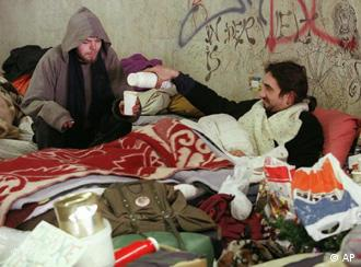 Two homeless men wrapped in blankets try to keep warm