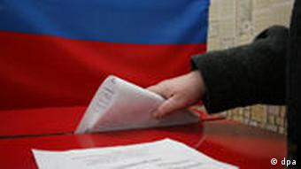 A hand putting a ballot into a ballot box in front of a Russian flag
