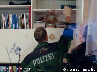A German police officer searching an office of a HNG member
