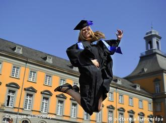 A woman celebrates graduation by jumping in the air