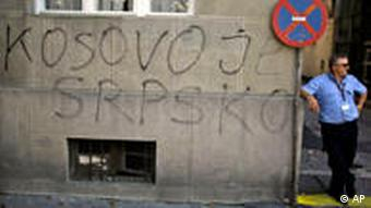 A man stands next to graffiti reading Kosovo is Serbian in Serbian Latin letters in Belgrade, Serbia, Thursday, Sept. 9, 2010. Serbia's government on Wednesday gave up its bid to challenge Kosovo's independence at the upcoming U.N. General Assembly meeting, after reaching a compromise solution with the EU over the resolution it tabled there. (AP Photo/Marko Drobnjakovic)