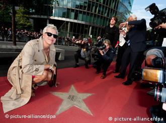 Die Regisseurin Doris Dörrie kniet neben ihrem Stern auf dem Boulevard der Stars, umringt von Fotografen (Foto: Robert Schlesinger / dpa).