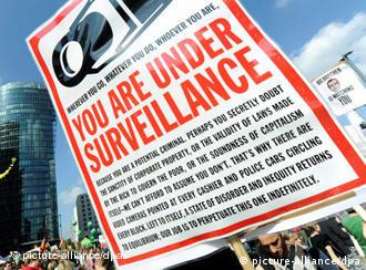 A sign at the demonstration reads You are under surveillance