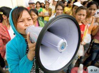 A Cambodian garment worker speaks on a loud speaker as she leads a strike in front of a factory