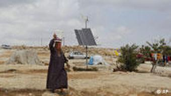 A Palestinian woman carries a bucket on her head as she passes a solar panel, in the West Bank village of Susya near Hebron,